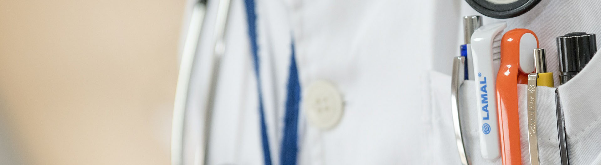 A doctor's white labcoat with his stethoscope around his neck and pens in his front pocket