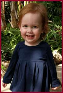 A young toddler with red hair smiles in front of some plants
