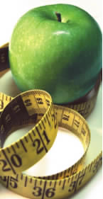 A green apple is wrapped up in a measuring tape commonly used to measure one's body
