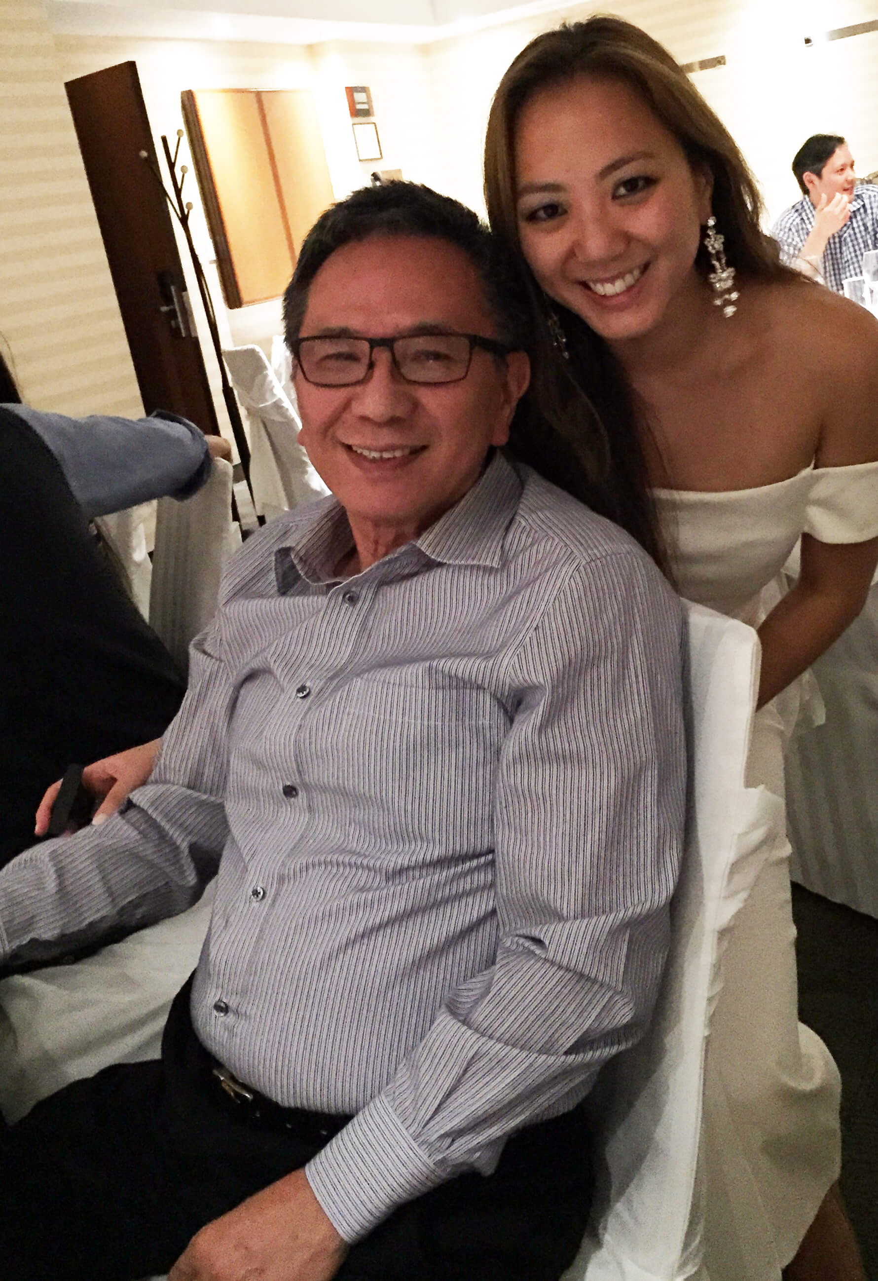 Serena leans behind her father who is seated in a chair at a banquet hall. Her arm is around him and they are both smiling
