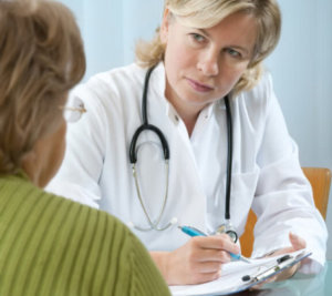 A doctor listens attentively while taking notes of what her patient is telling her. She is wearing a stethoscope and writing with pen on a clipboard. The patient is a middle-aged woman her glasses, and her back to the camera.