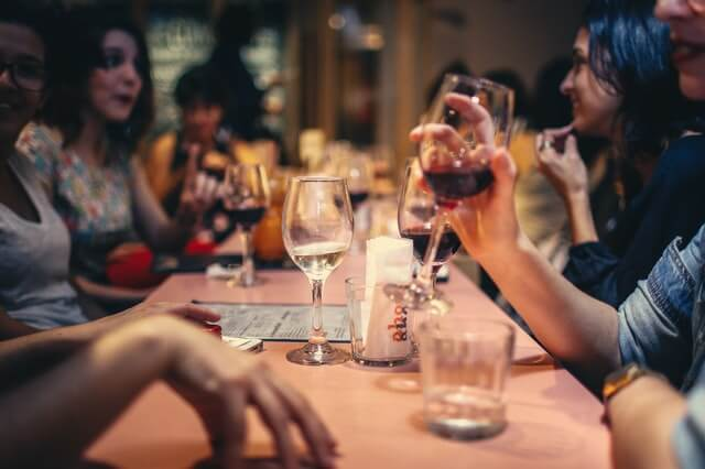 Men and women sit together at a long restaurant table, engaged in conversation. There are menus, salt shakers and glasses on the table. Three women hold glasses of red wine, while other glasses containing red wine, white wine and liquor are scattered across the long table.