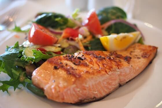 A piece of grilled salmon sits on a bed of lettuce with tomatoes, onions and a slice of lemon pictured in the background.